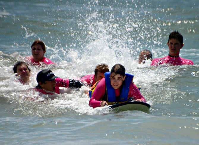 Each_surfer_was_surrounded_by_swimmers_who_could_help_out_in_case_they_fell_off_the_board